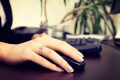 Blondynka bizneswoman pracuje na komputerze przy biurem Ostrość jest na ręce, myszy/ Obrazy Stock