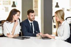 Blondynka bizneswoman wyjaśnia z laptopem uśmiechnięty młody cou Obraz Stock