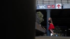 Blondynka chodzi tupiąc od incontinence i przylega filar podczas gdy czekający zwrot toaleta zakupy zbiory