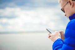 Blondynka mężczyzna używa telefon komórkowego przy jeziorem obraz royalty free