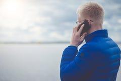Blondynka mężczyzna używa telefon komórkowego przy jeziorem fotografia stock