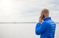 Blondynka mężczyzna używa telefon komórkowego przy jeziorem obrazy stock