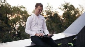 Blondynka młody człowiek w białym koszulowym wydaje czasie używać pastylki radio Ono uśmiecha się blisko, szczęśliwy mężczyzna ob zdjęcie wideo