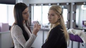 Blondynka model zapobiega makijażu artysty malować jej wargi ochronny połysk Wzorcowy opowiadać z jego dziewczyną, zbiory
