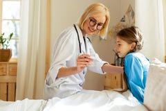 Blondynka pediatra pokazuje chorej dziewczynie wskaźniki przy termometrem obraz stock
