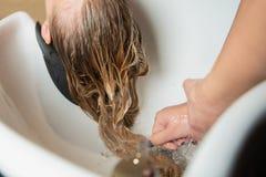 Blondynka włosy domycie z szamponem w luksusowym piękno salonie fotografia royalty free