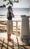 Blondynka w długiej spódnicowej pozyci na drewnianym moscie na tle ranku morze i przystosowywa jej kolczyki A Obrazy Stock