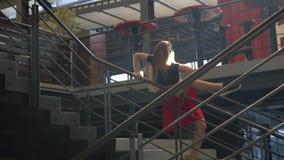 Blondynka z długim w czerwonej spódnicie i czarny temat pozuje na schodkach w zakupy i spojrzeniach popieramy kogoś, wolny moiton zbiory