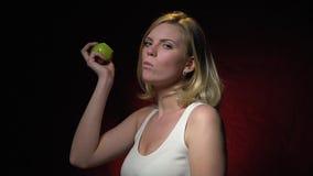 Blondynka z dużymi piersiami gryźć daleko zielonego jabłka zbiory wideo