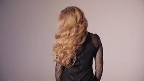 Blondynki ładna dama dotyka wspaniałych kędziory w czerni sukni zbiory wideo
