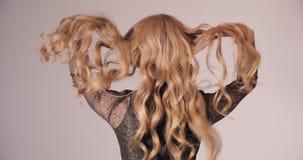 Blondynki ładna dama dotyka wspaniałych kędziory w czerni sukni zbiory