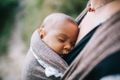Blondynki caucasian mama trzyma jej barwionego dziecka w temblaku obrazy royalty free