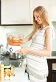 Blondynki ciężarnej gospodyni domowej kulinarni warzywa z elektrycznym ste Zdjęcia Stock