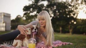 Blondynki długa z włosami kobieta kłaść dalej na szkockiej kracie w parku i próbuje robić selfie fotografii z jej spanielem używa zdjęcie wideo