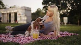 Blondynki długa z włosami kobieta kłaść na ziemi w parku na szkockiej kraty ściółce i pieści jej małego psa zamazujący tło zbiory wideo