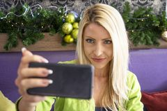 Blondynki dziewczyna bierze selfie w kawiarni obrazy royalty free