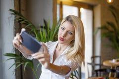 Blondynki dziewczyna bierze selfie w kawiarni zdjęcia stock