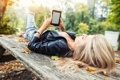 Blondynki dziewczyna czyta ebook lying on the beach na drewnianym stole w jesień parku zdjęcia royalty free