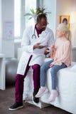 Blondynki dziewczyna jest ubranym cajgi i różową bluzkę siedzi blisko lekarki zdjęcie stock
