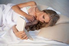 Blondynki dziewczyna kłama w łóżku i czytaniu przy pora snu książka Zdjęcia Stock