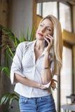 Blondynki dziewczyna opowiada na telefonie w kawiarni zdjęcie stock