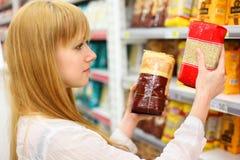 Blondynki dziewczyna porównuje ryż w sklepie obrazy stock