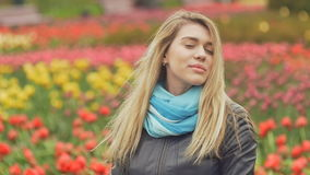 Blondynki dziewczyna pozuje z poważnym spojrzeniem przy tłem park kwiaty zbiory wideo