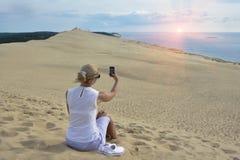 Blondynki dziewczyna robi selfie dla instagram przy Pyla diuną wielka piasek diuna w Europa obrazy stock