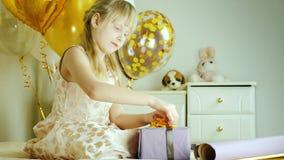 Blondynki dziewczyna 7 rok zawijał pudełko prezenty w papierze Urodzinowych prezentów pojęcie zbiory