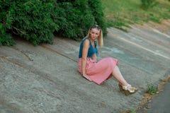 Blondynki dziewczyna w błękita świetle i wierzchołku - różowa spódnica w chodakach, jest ubranym okulary przeciwsłonecznych siedz zdjęcie stock