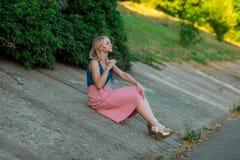 Blondynki dziewczyna w błękita wierzchołku i świetle - różowa spódnica jest ubranym okulary przeciwsłonecznych siedzi na skłonie  zdjęcie royalty free