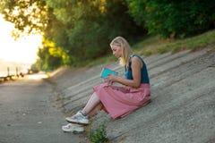 Blondynki dziewczyna w błękita wierzchołku i świetle - różowa spódnica w sneakers siedzi na skłonie drogowa powierzchnia, czytają zdjęcie stock