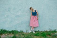 Blondynki dziewczyna w błękita wierzchołku i świetle - różowa spódnica w sportów butów spojrzenia puszku, tanczy na tle błękit śc zdjęcie stock