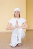 Blondynki dziewczyna w biały ćwiczy joga w pozyci Ardha Padmasana Zdjęcie Royalty Free