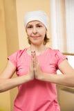 Blondynki dziewczyna w biały ćwiczy joga w pozyci Ardha Padmasana Obraz Stock
