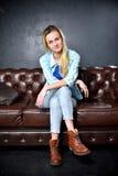 Blondynki dziewczyna w cajgach siedzi na rzemiennej kanapie fotografia royalty free