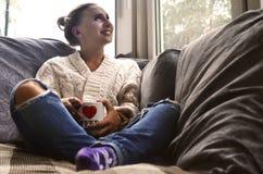 Blondynki dziewczyna w ciepłym pulowerze z filiżanki kawy obsiadaniem na a zdjęcia royalty free