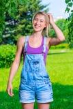 Blondynki dziewczyna w kombinezonach pozuje w parku obraz stock