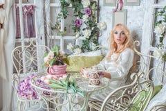 Blondynki dziewczyna w pokoju z kwiatami obraz stock