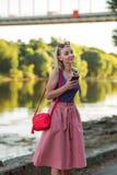 Blondynki dziewczyna w purpurach nakrywa i światło - różowa spódnica z małą czerwoną naramienną torbą pisze SMS w wiszącej ozdobi obraz stock