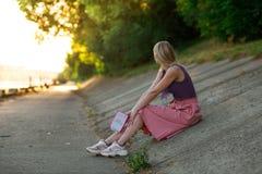 Blondynki dziewczyna w purpurach nakrywa i zaświeca - różowa spódnica w sneakers siedzi na skłonie drogowa powierzchnia, czyta ks obrazy royalty free