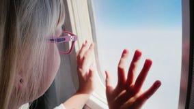 Blondynki dziewczyna w różowych szkieł spojrzeniach przy samolotowym okno na chmurach zbiory