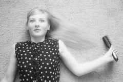 Blondynki dziewczyna z gręplą w jego ręce, magnesujący zgrzywiony włosy Fotografia Stock