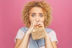 Blondynki dziewczyna z kędzierzawym włosy loking prosto i próbuje dmuchać papierową torbę Przeraża i okalecza odosobniony zdjęcia stock
