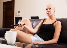Blondynki dziewczyna z pilot do tv zdjęcie royalty free