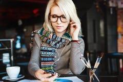 Blondynki dziewczyna z telefonem komórkowym i hełmofonami Zdjęcia Royalty Free