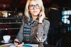 Blondynki dziewczyna z telefonem komórkowym i hełmofonami Obraz Royalty Free