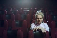 Blondynki dziewczyny dopatrywania film w pustym teatrze Obrazy Royalty Free