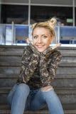 Blondynki dziewczyny obsiadanie na schodkach i uśmiechu obraz royalty free