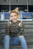 Blondynki dziewczyny obsiadanie na schodkach i uśmiechu obrazy stock